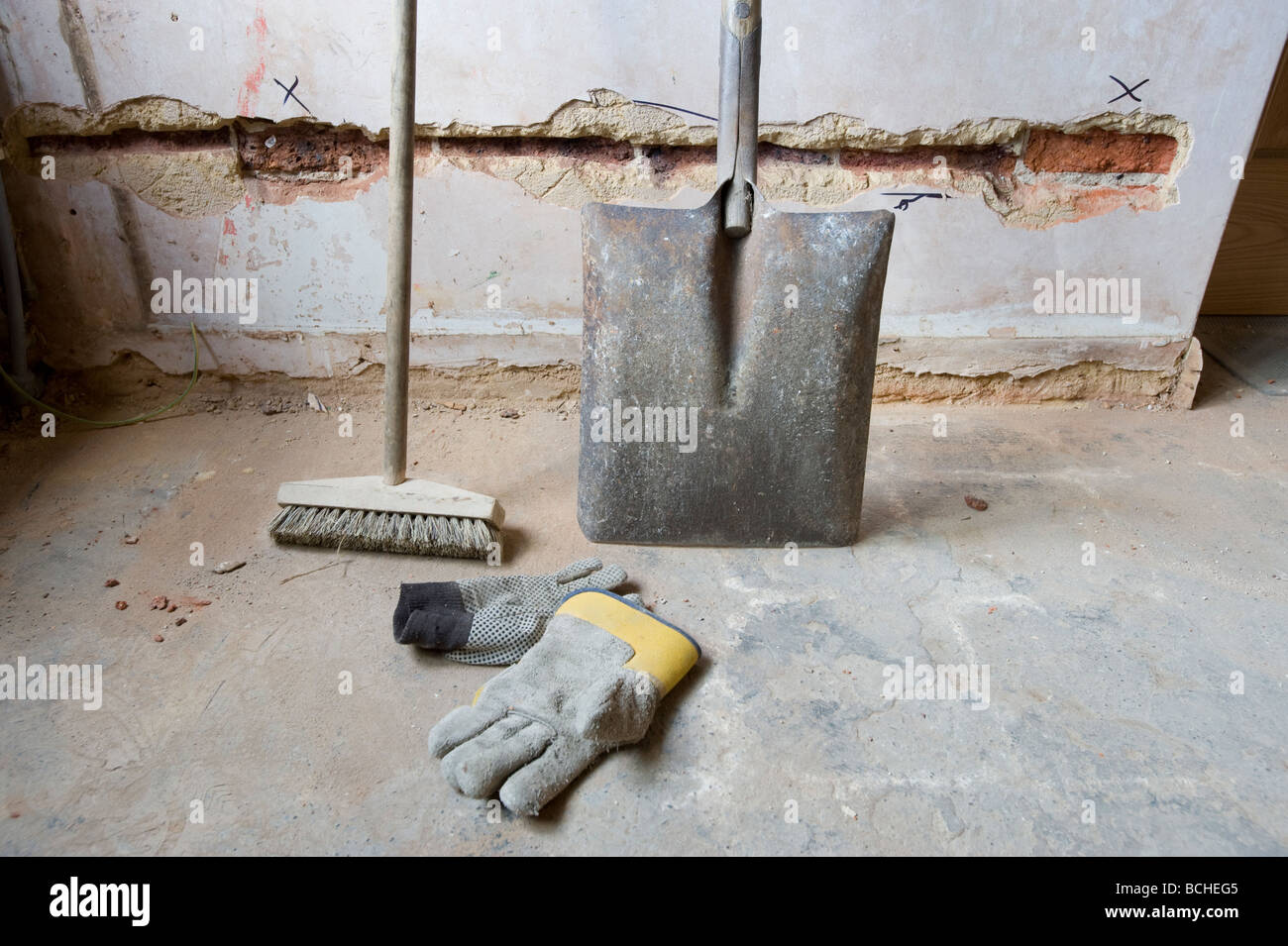 SHOVEL BRUSH AND GLOVES ON FLOOR OF A CONSTRUCTION SITE DURING REFURBISHMENT. - Stock Image