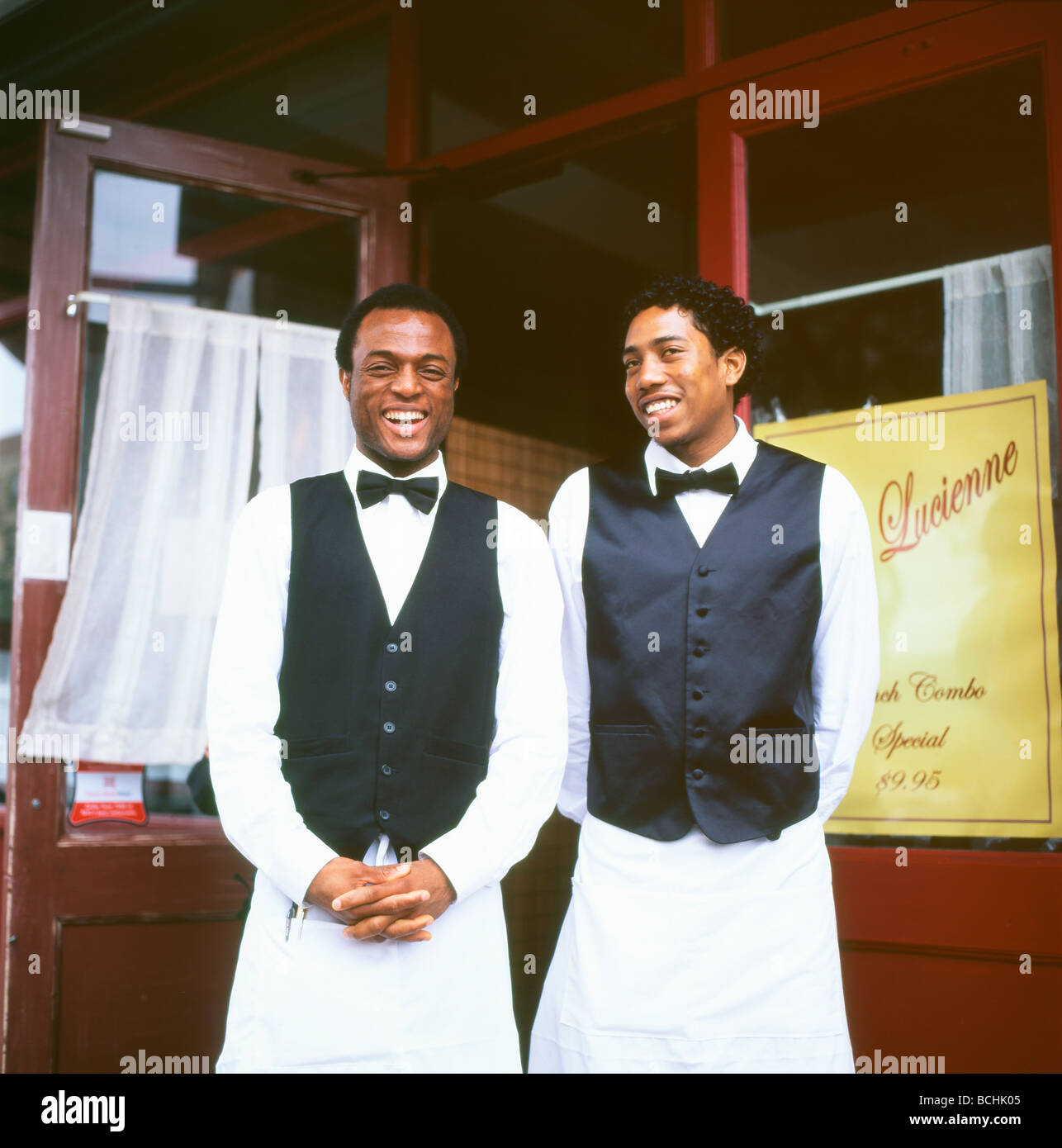Two waiters in aprons and bow ties greeting customers outside Chez Lucienne restaurant Harlem New York City, NY - Stock Image