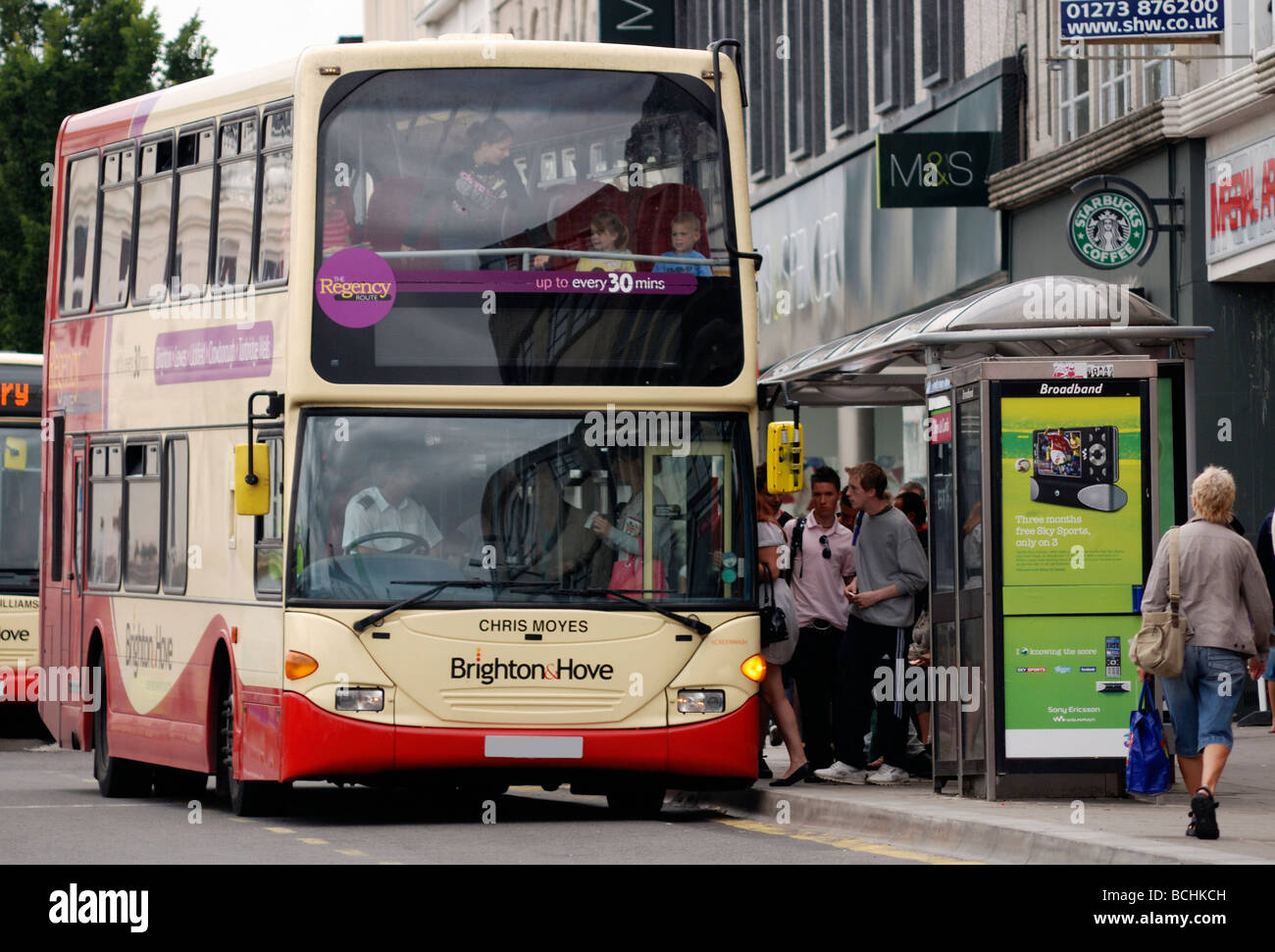 Double decker bus pulling into busy bus stop - Stock Image