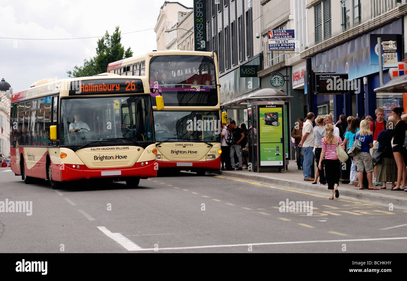 A bus passing another one as it picks up passengers from a bus stop - Stock Image