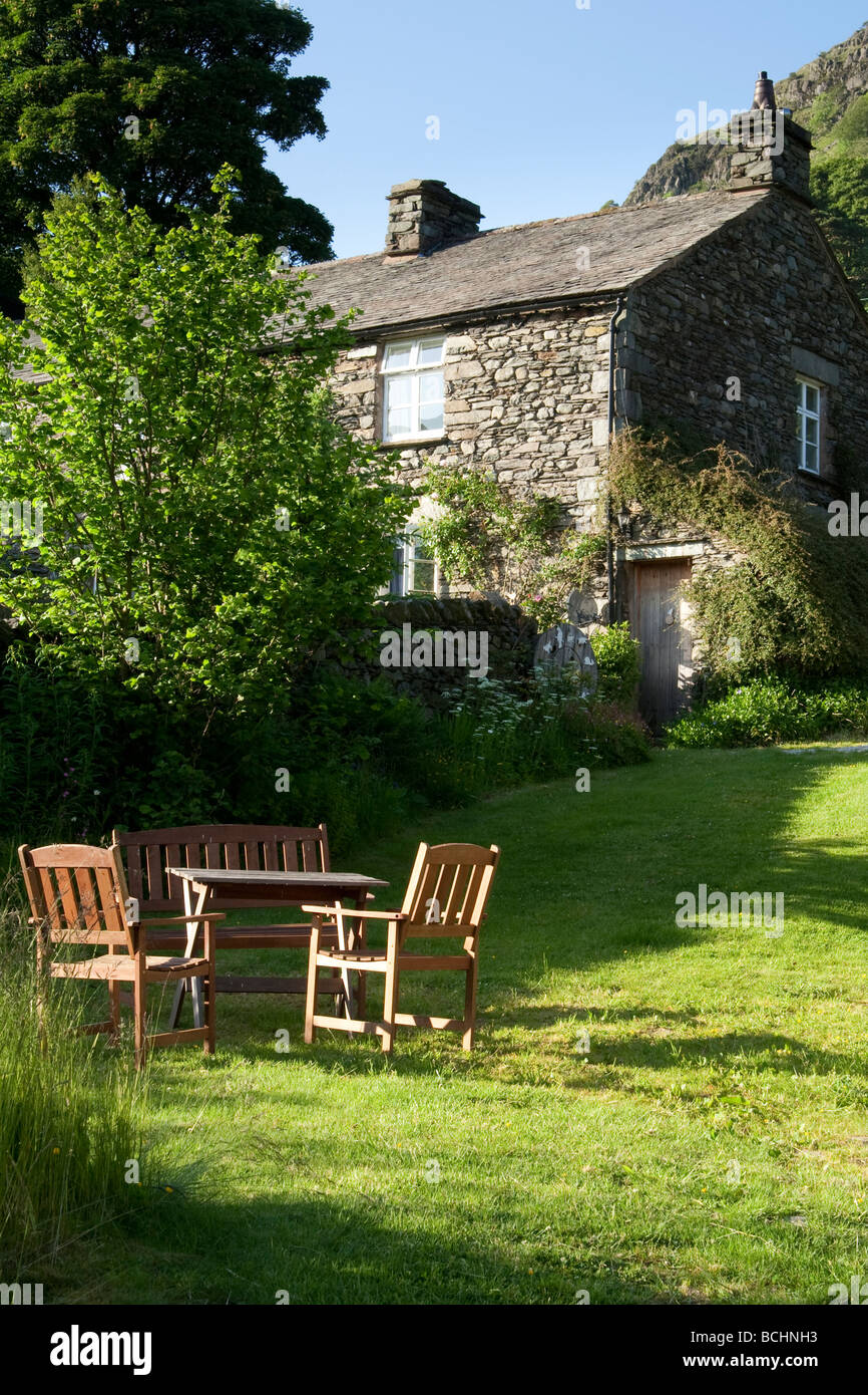 Table and chairs in a cottage garden, UK. - Stock Image