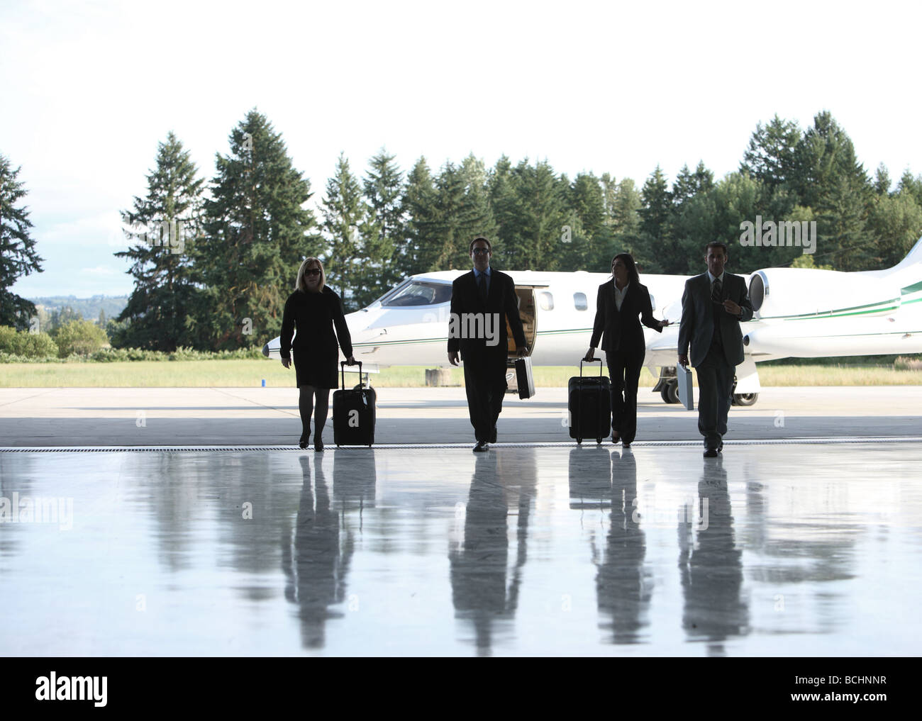 Group of businesspeople walking to corporate jet - Stock Image