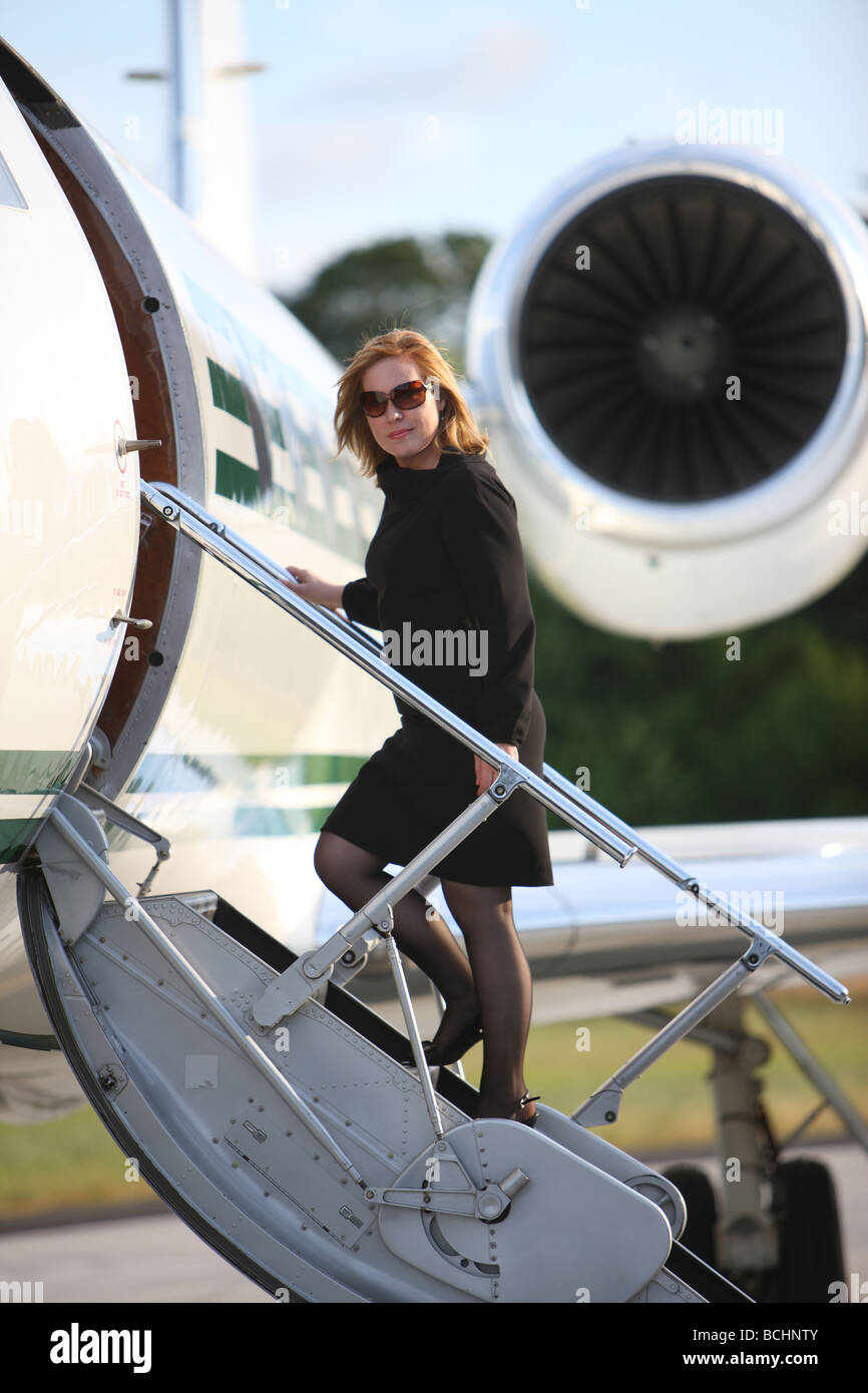 Businesswoman standing on stairs to private jet - Stock Image