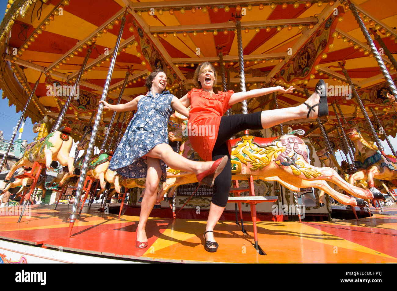 Two girls on a day out in Brighton larking about on the carousel on the beach. - Stock Image