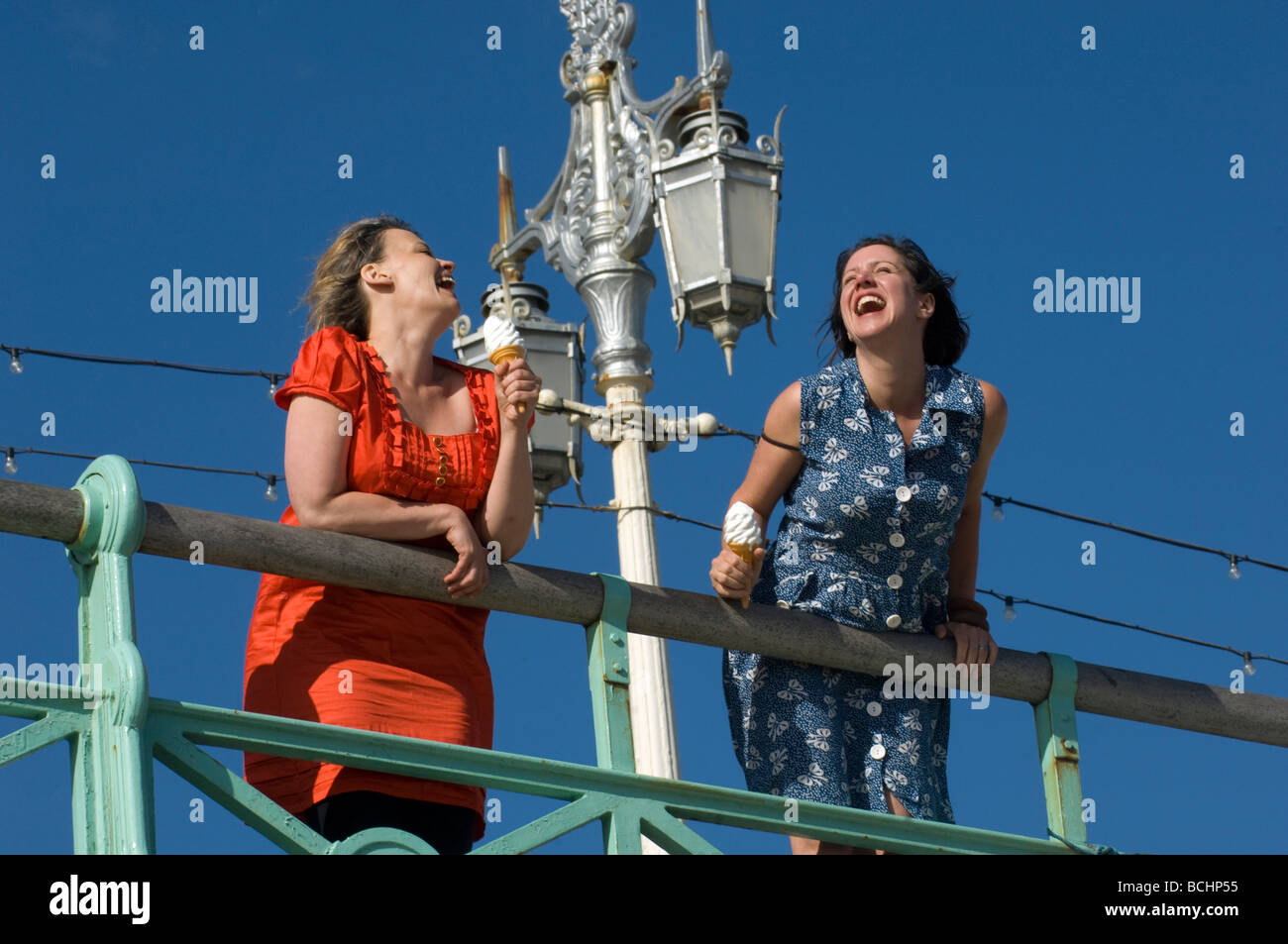 Two girls on the Prom at Brighton with icecream, laughing, having fun. - Stock Image