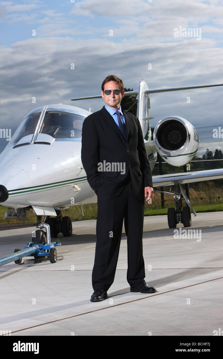 Businessman standing in front of corporate jet - Stock Image