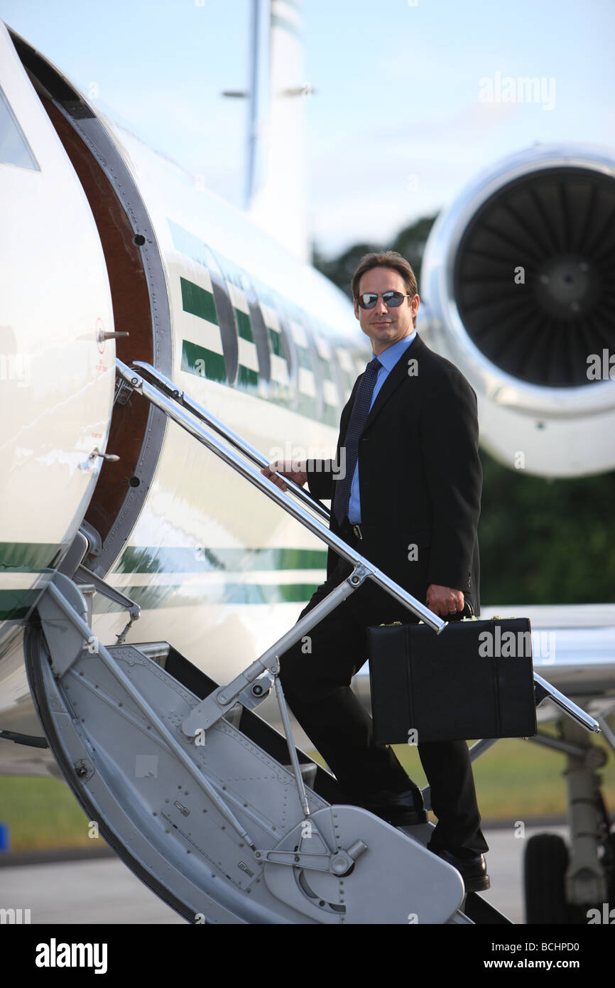 Businessman standing on stairs to private jet - Stock Image