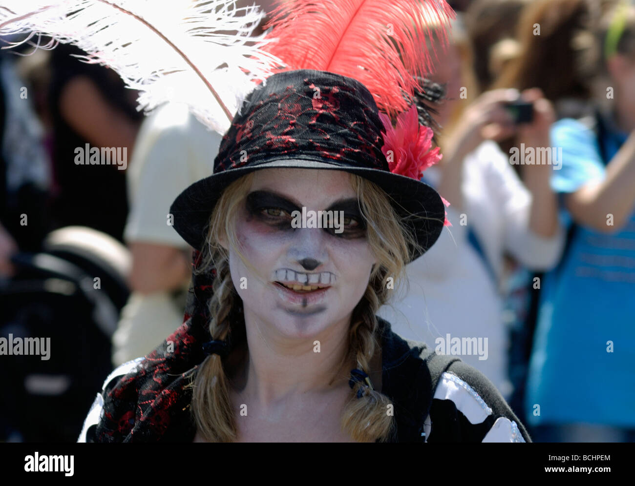 Girl in goth facepaint face paint and feathered hat in street parade - Stock Image