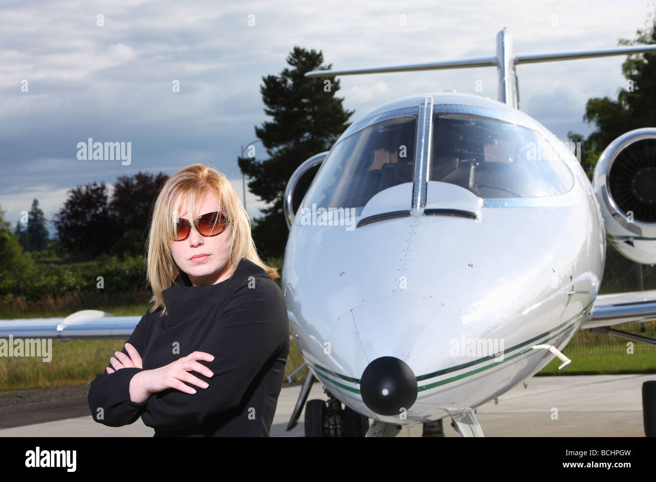 Businesswoman standing by corporate jet - Stock Image