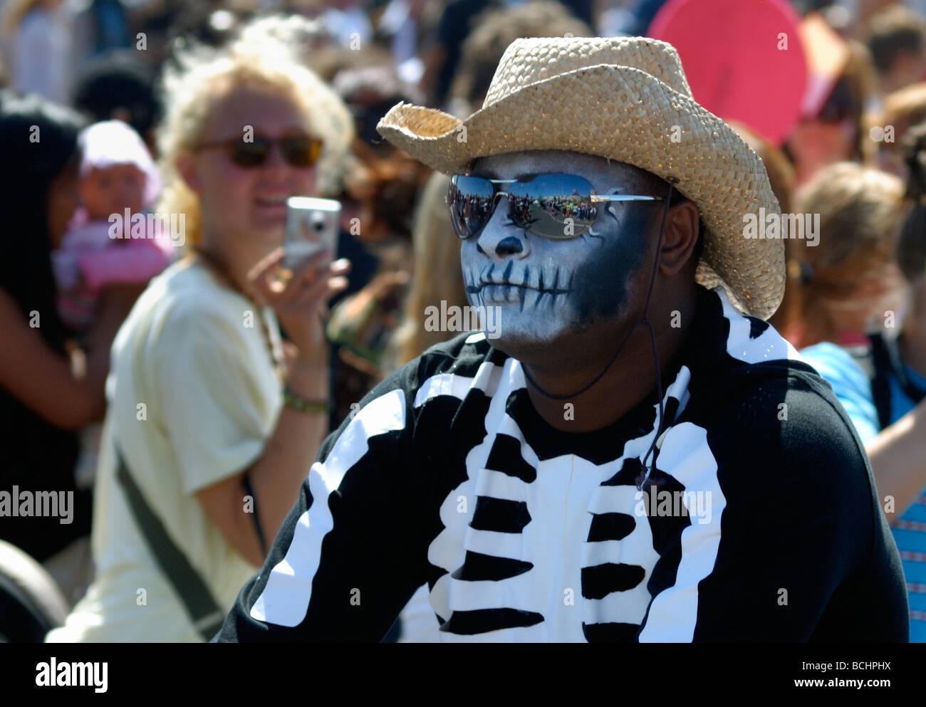 Black man dressed as skeleton with sunglasses and straw hat in street parade - Stock Image