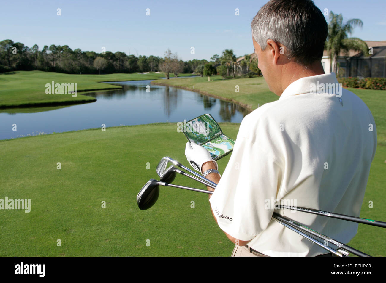 A Golfer studies a course card before teeing off. - Stock Image