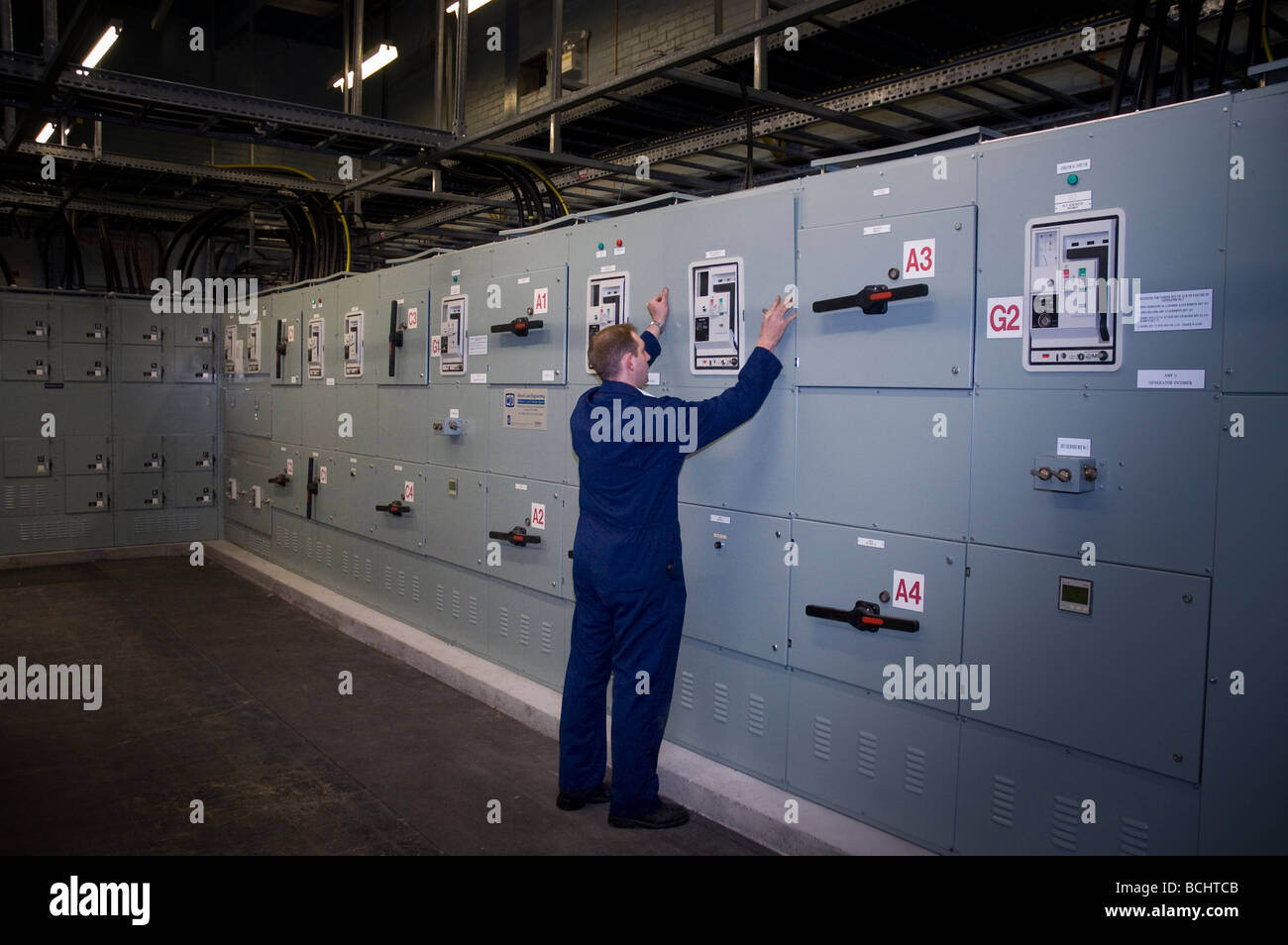 Engineer at Large electrical control panel in plant room Stock Photo ...