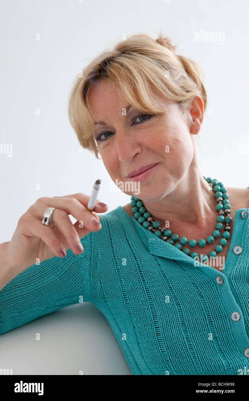 Senior woman is smoking a cigarette - Stock Image