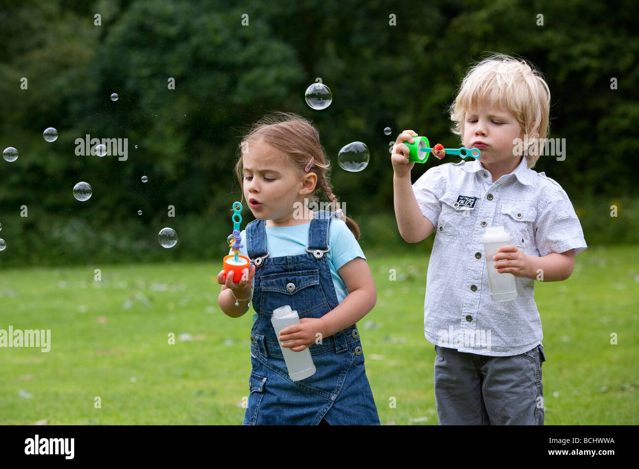 Two toddlers blowing bubbles - Stock Image