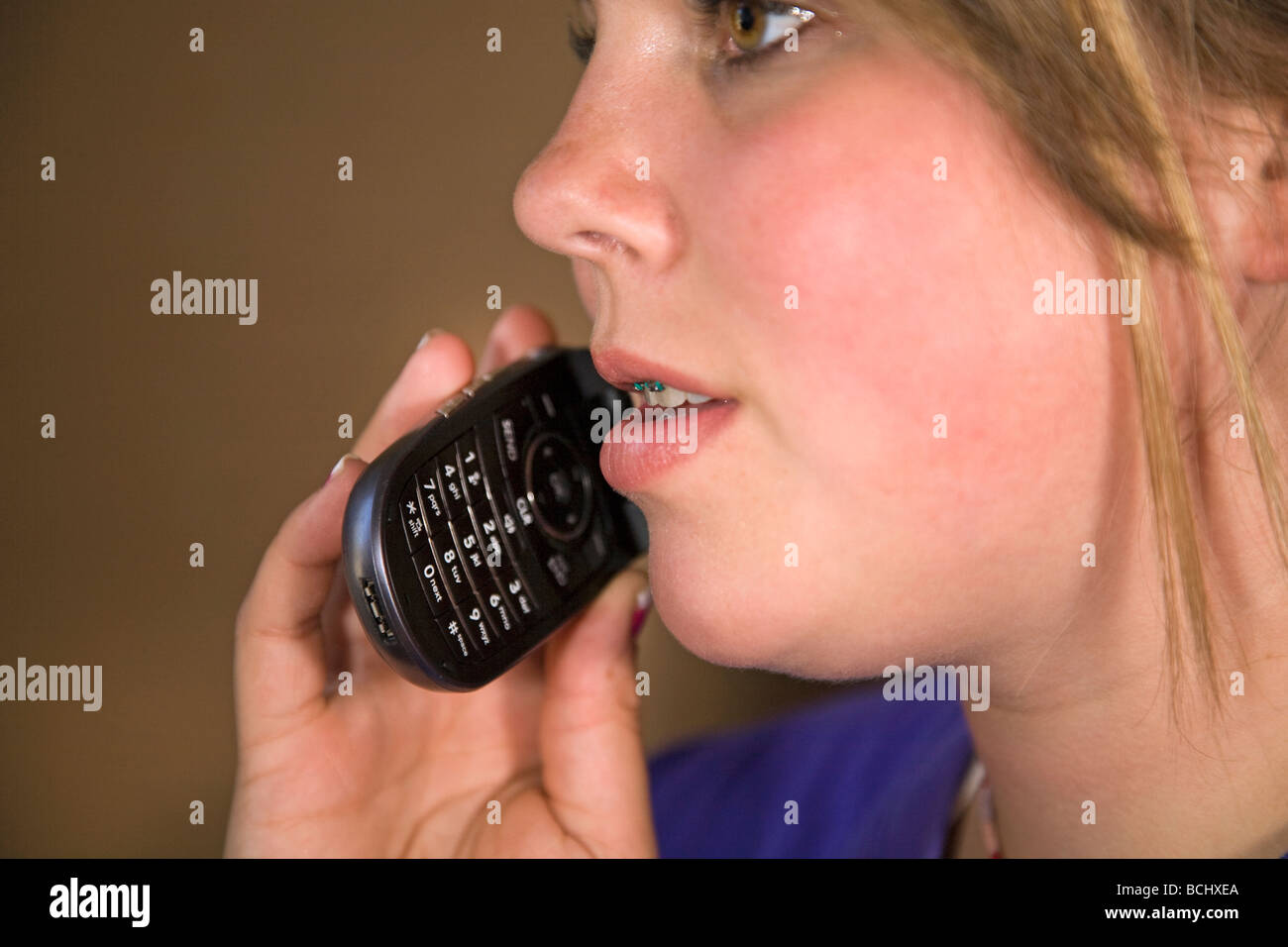 A teenager with braces talking on cell phone or a flip phone. - Stock Image
