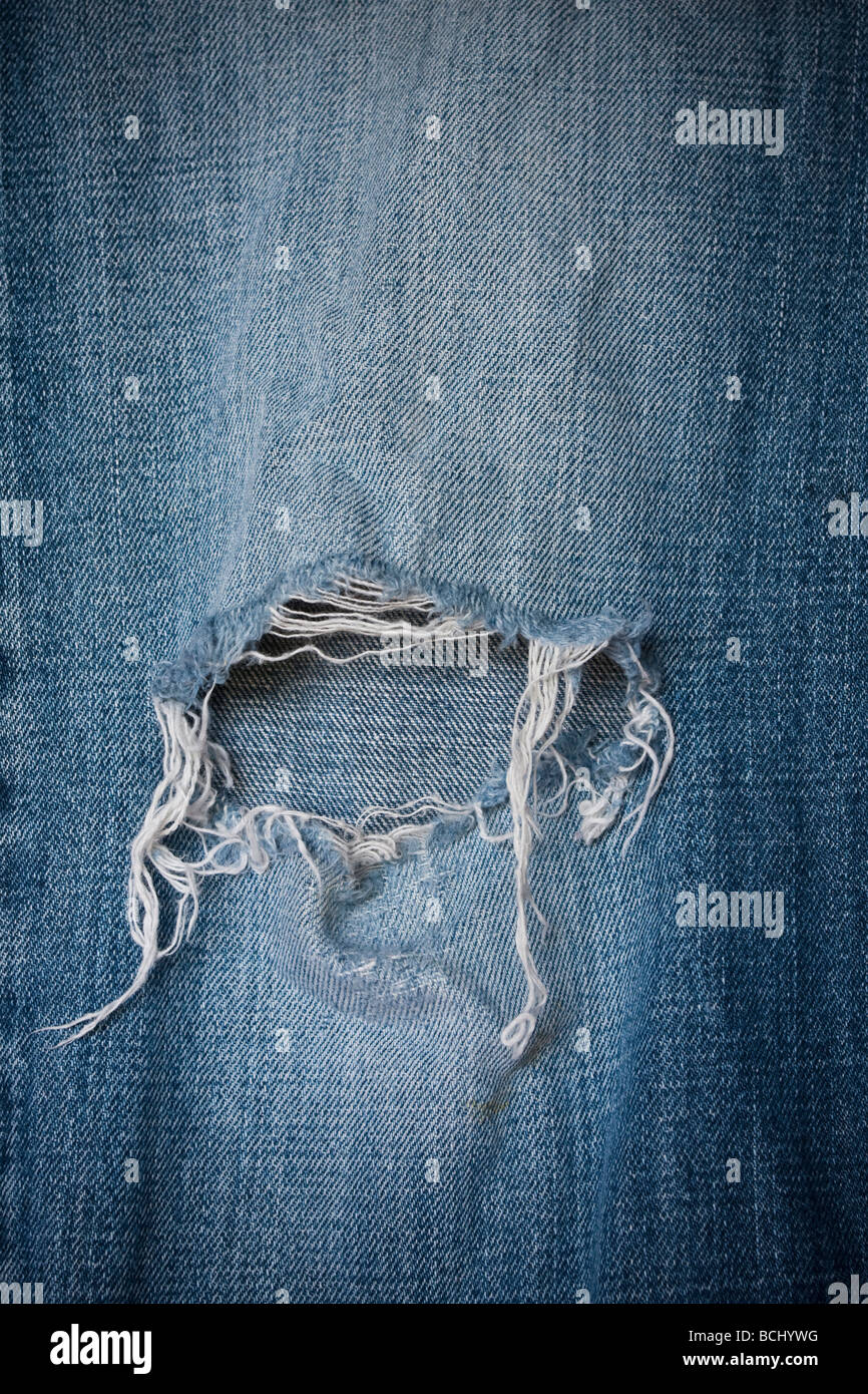 Detail of a frayed hole in the knee of a pair of denim jeans - Stock Image
