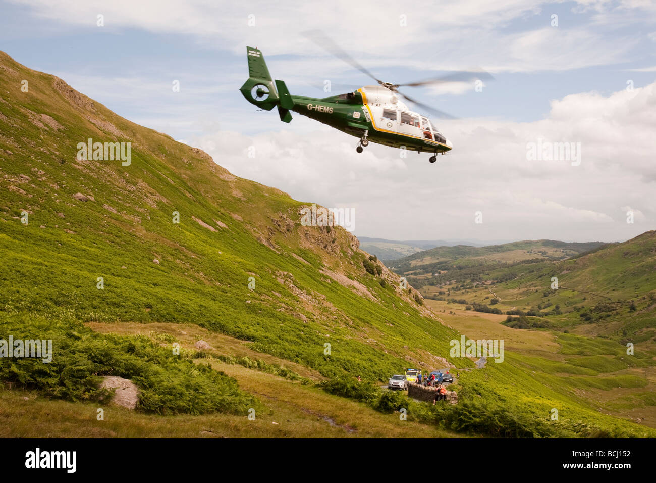 An Air Ambulance takes off with a casualty from a mountain rescue on Wrynose Pass, Lake District, UK - Stock Image
