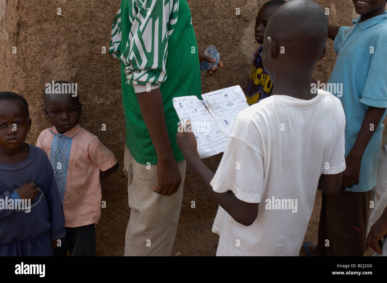 child reading exercise book in street in village in Tamale, Ghana - Stock Image
