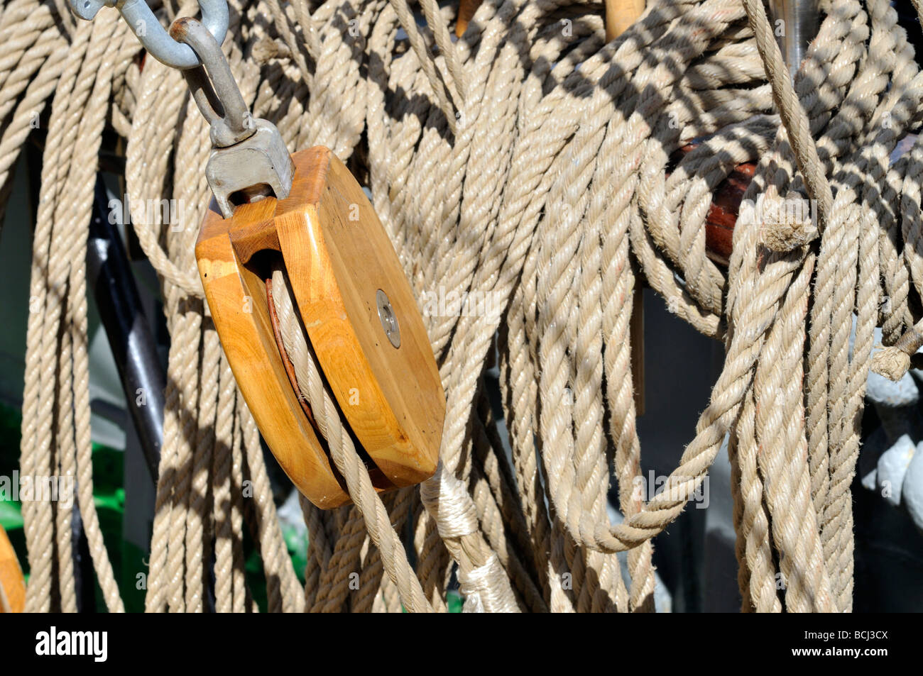 Closeup of single wood block on tall ship surrounded by lines and rigging - Stock Image