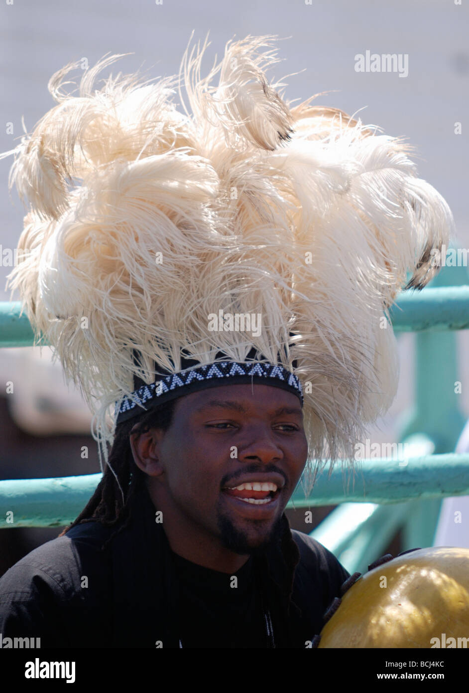 Black man in headdress playing music - Stock Image