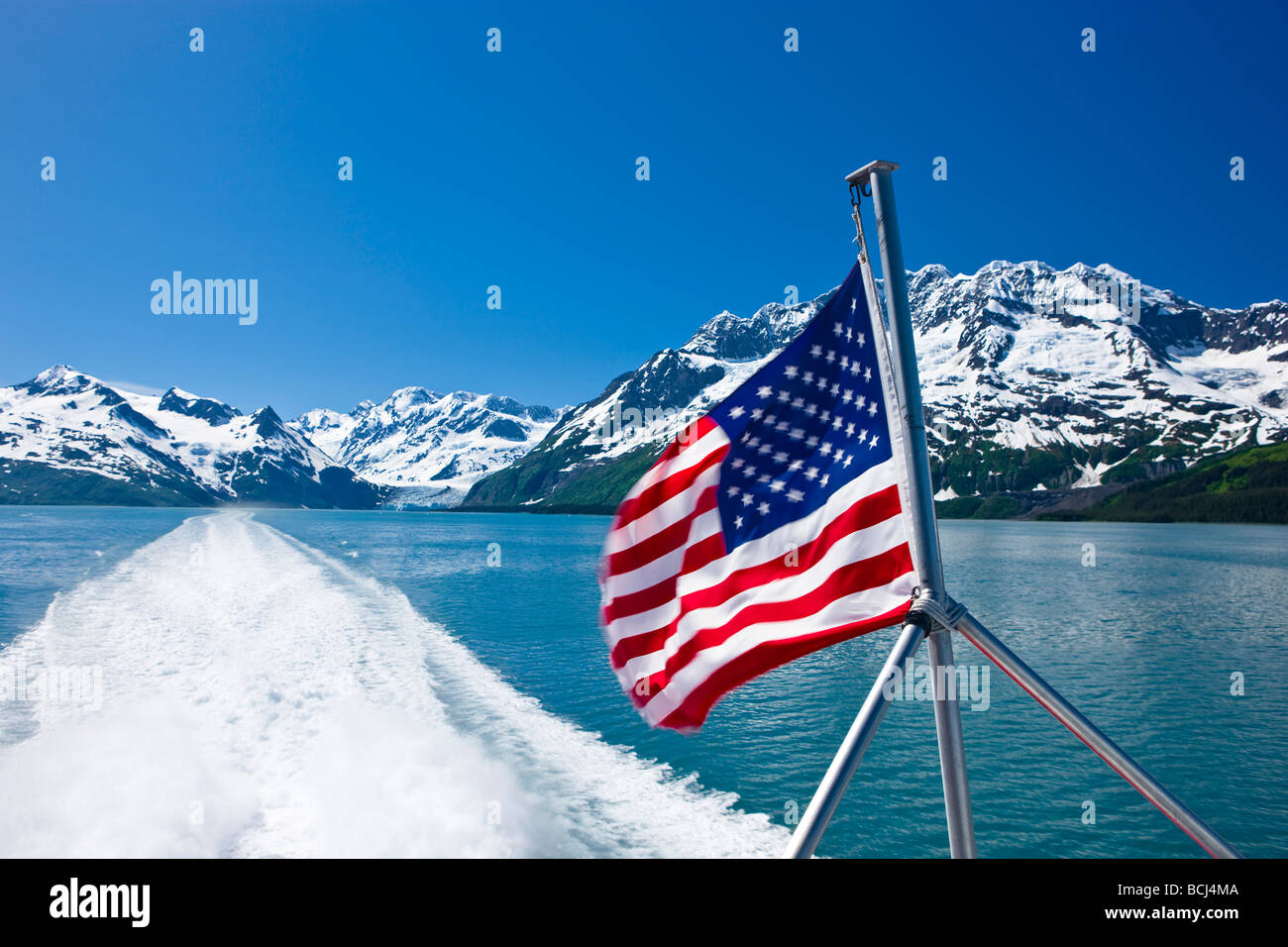 View of Prince Wiliam Sound and the American flag flown from the deck of a tour boat, Prince William Sound, Alaska - Stock Image