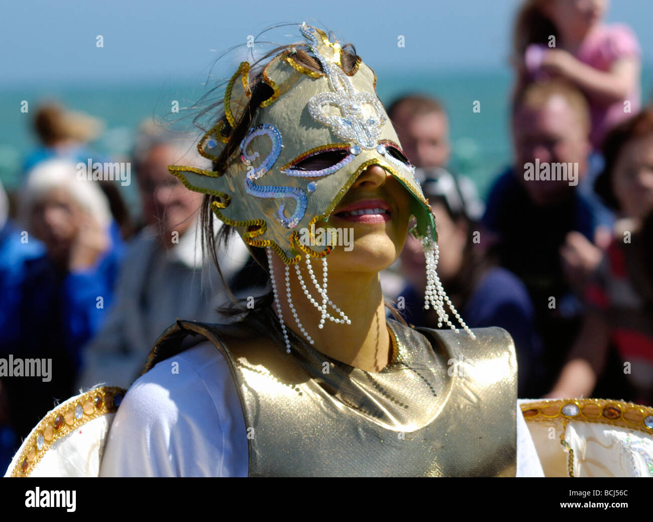 Girl in silver costume and mask in street parade - Stock Image