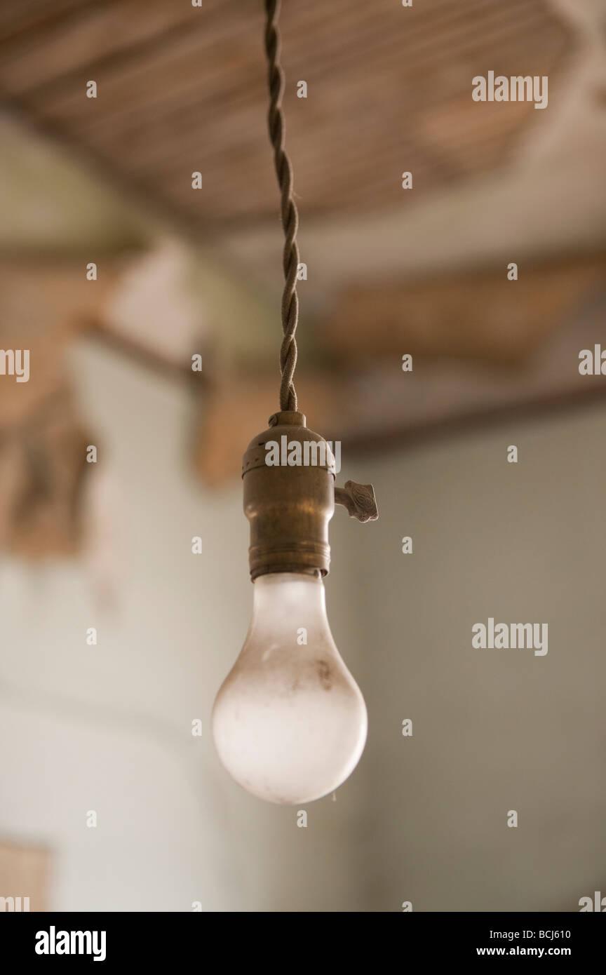 Old light fixture light bulb socket and bulb hanging - Stock Image