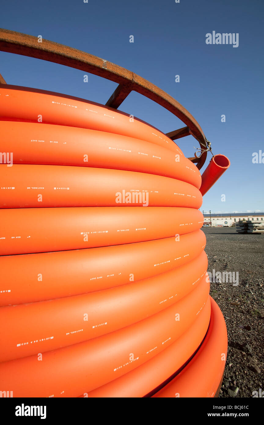 Spool of orange telecommunication cable against sky - Stock Image