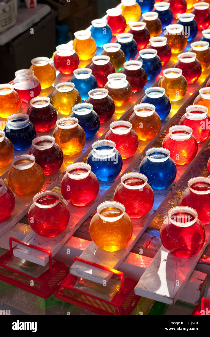 Rows of jars filled with colored water at arcade game at carnival fair festival - Stock Image