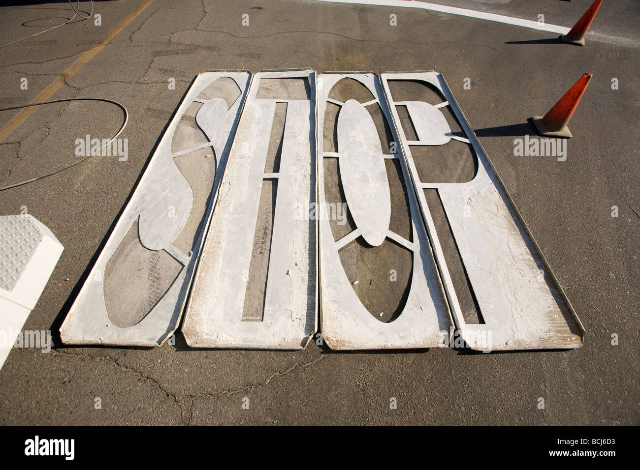 Wood stencils for painting STOP on pavement laying on asphalt street with orange traffic cones Indio California - Stock Image