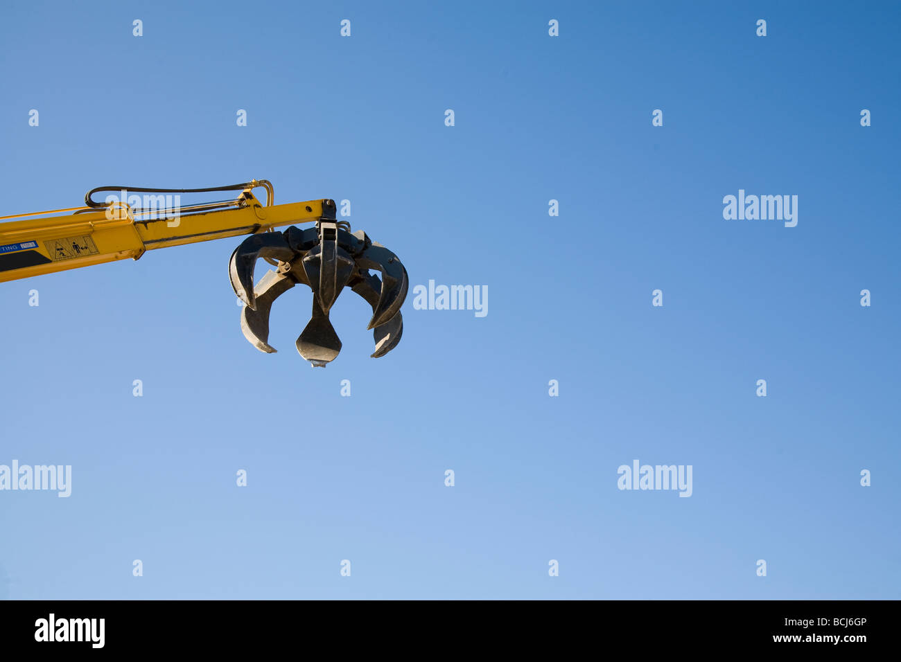 Claw of yellow mechanical machine used for picking up scrap metal at reclycling yard against blue sky Indio California - Stock Image