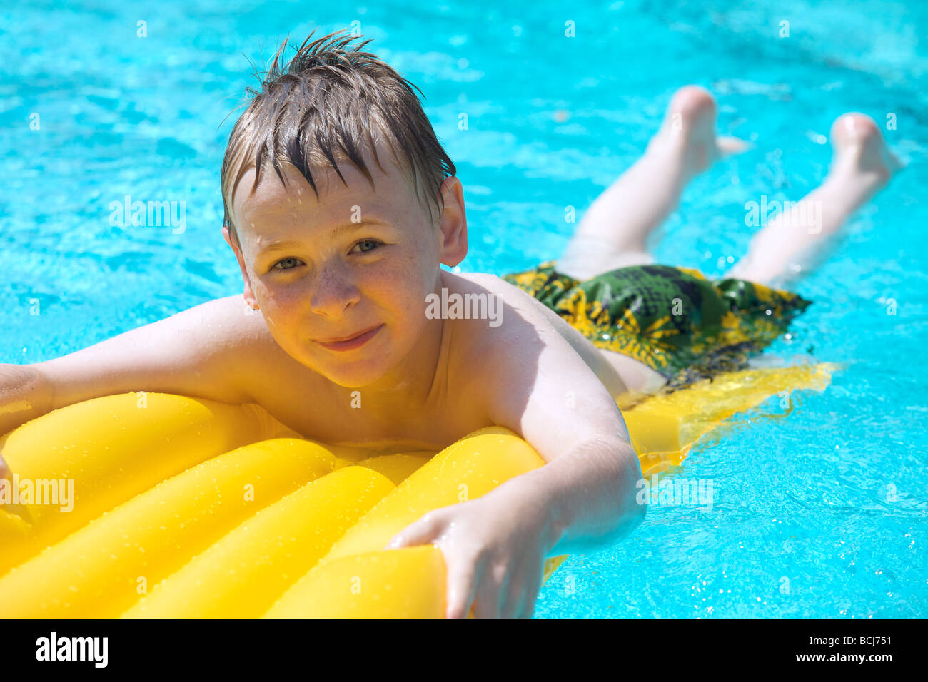 Happy Young Boy Relaxing At The Swimming Pool On A Yellow