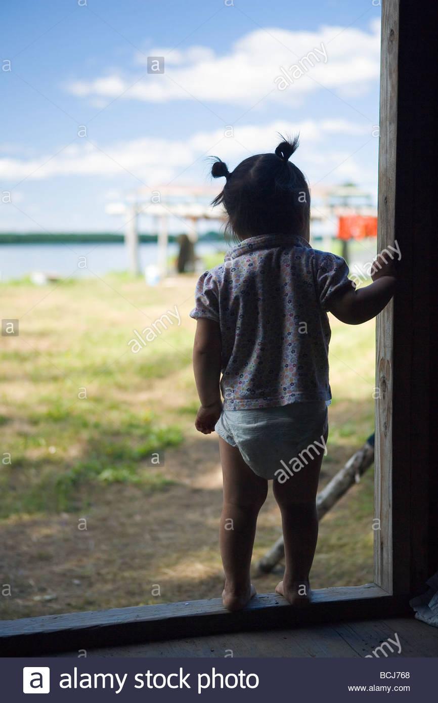 Small native Yupik girl standing in doorway of cabin watching family fish on Kuskokwim River Alaska - Stock Image