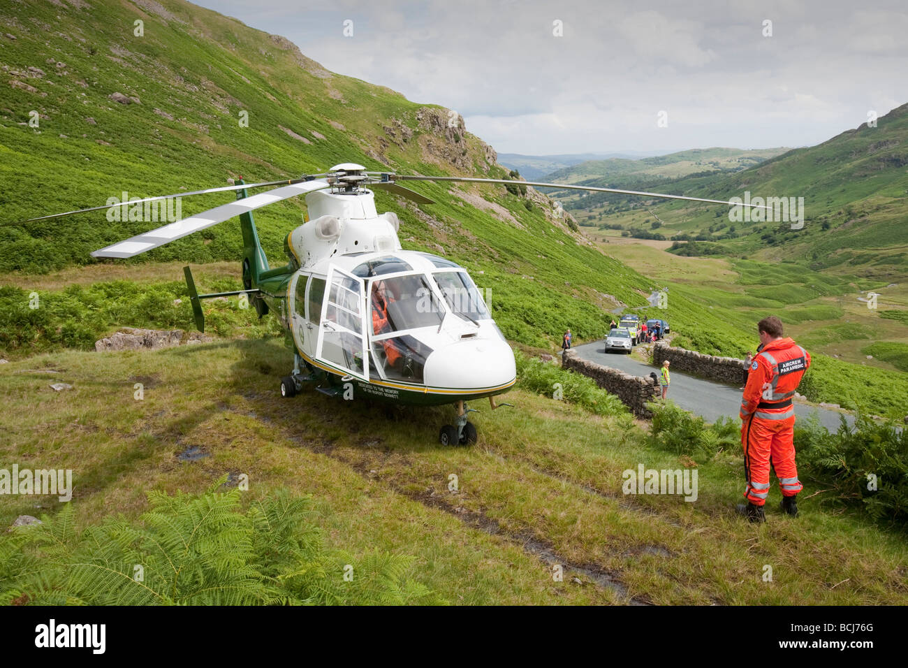 An Air Ambulance prepares to takes off with a casualty from a mountain rescue on Wrynose Pass, Lake District, UK - Stock Image