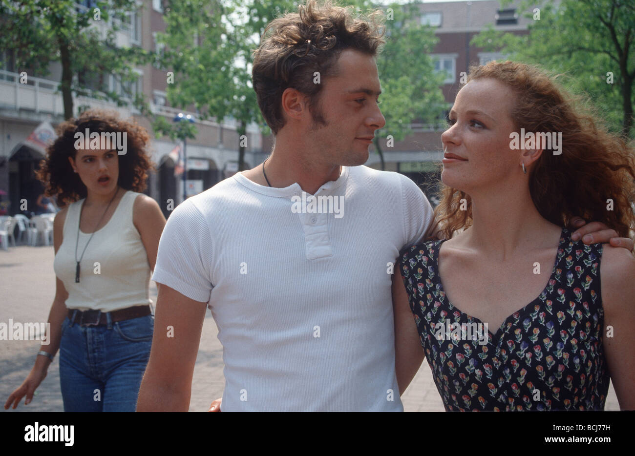 Cheating couple walking in street and being exposed. - Stock Image