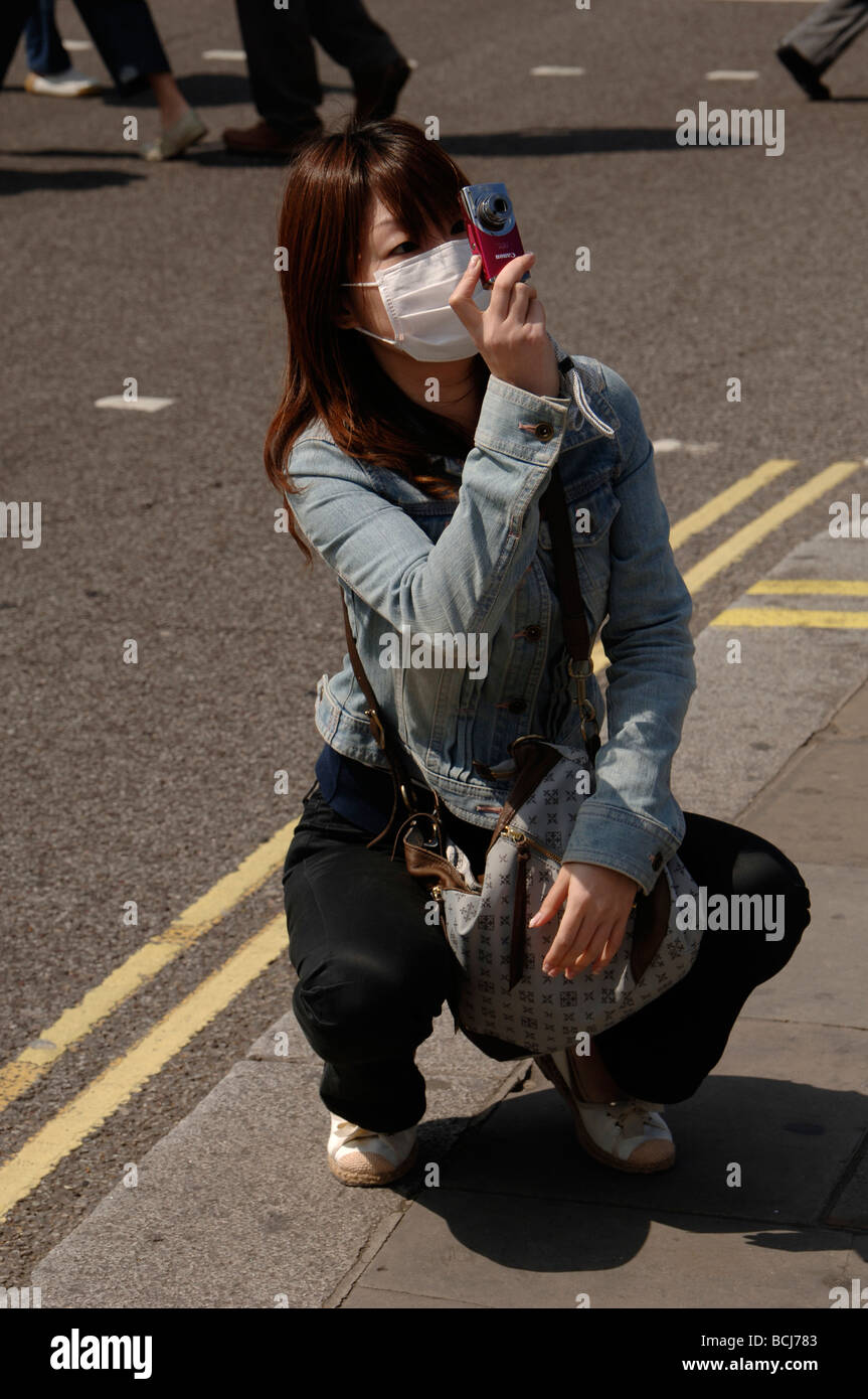 asian girl tourist wearing a protective face mask to prevent swine flu in trafalgar square London - Stock Image