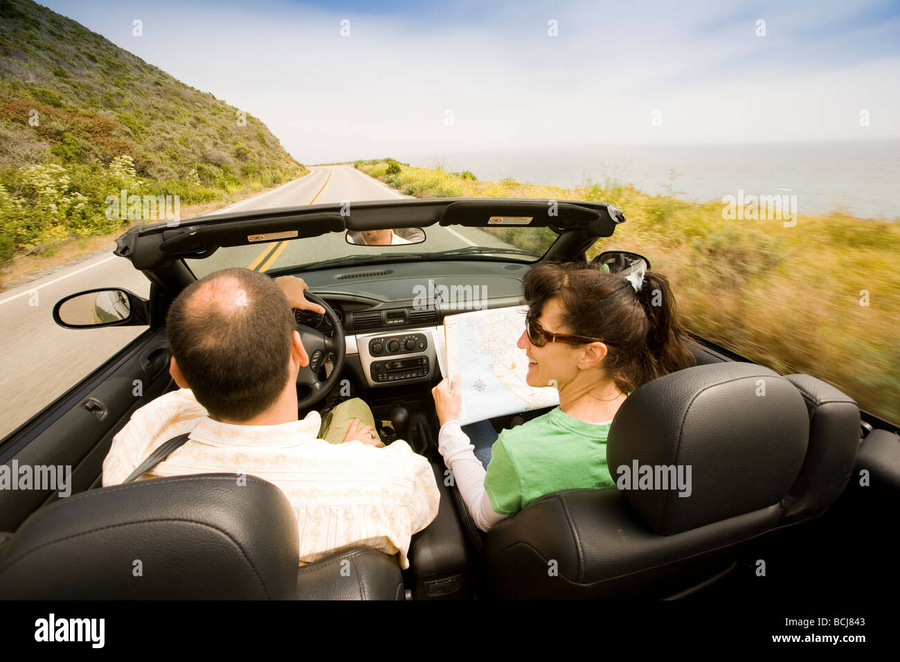 Caucasian male and female in moving convertible car on Highway 1 in Big Sur California USA Female is holding road - Stock Image