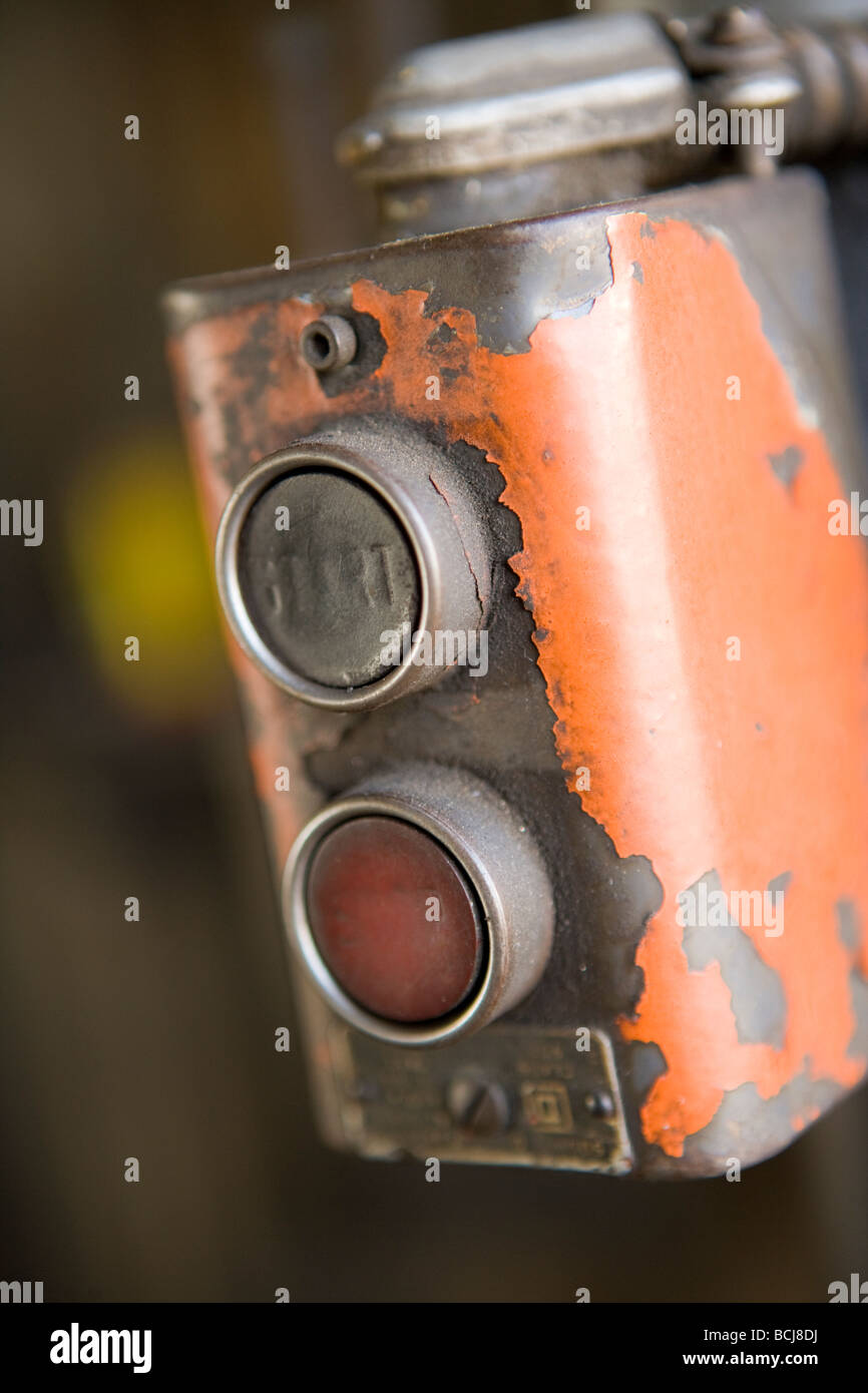 Detail of factory machine controls with push buttons for START and STOP Control box has chipped orange paint - Stock Image