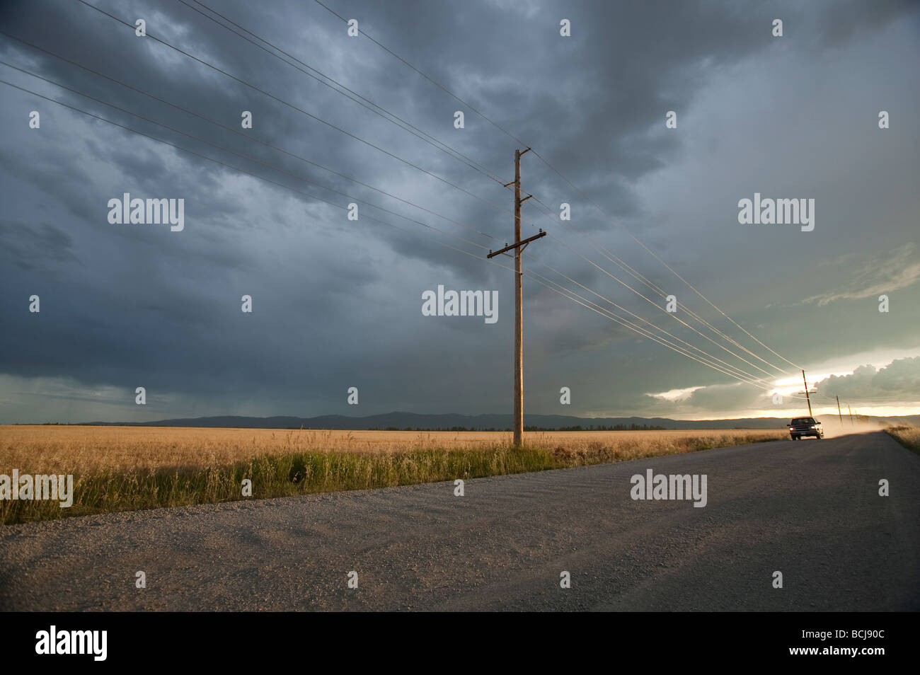 Truck SUV vehicle automobile on unpaved gravel road lined with utility poles at sunset with dramatic sky Montana - Stock Image