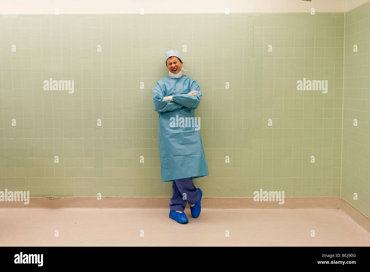 Caucasian male surgeon/doctor in blue surgical scrubs leaning against green tile wall yawning. - Stock Image