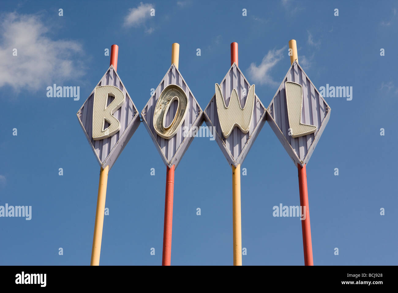 Bowling alley sign that says BOWL in diamond shapes Multi colored poles sky background - Stock Image