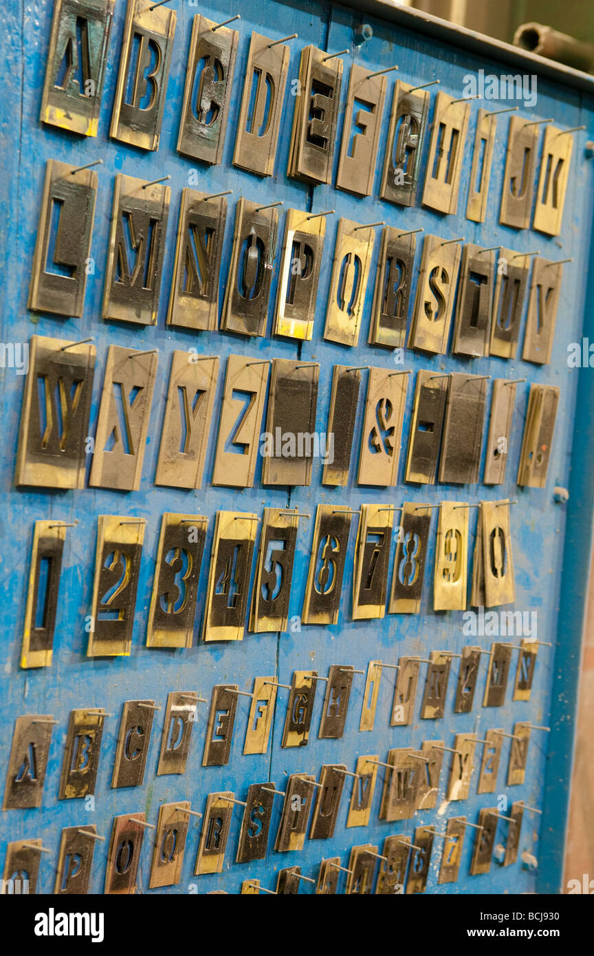 metal letter stencils hanging on blue wall rack in factory