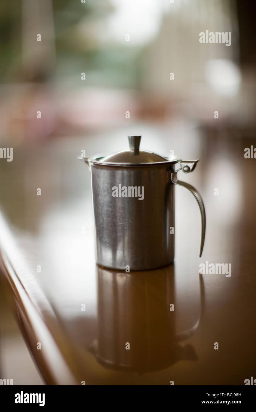 Detail of stainless steel cream milk dispenser on counter of cafe restaurant diner Shallow focus Crescent City California - Stock Image