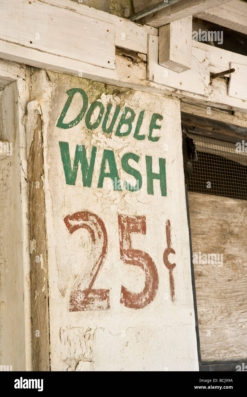 Old sign painted on laundromat building wall reads Double Wash 25 - Stock Image