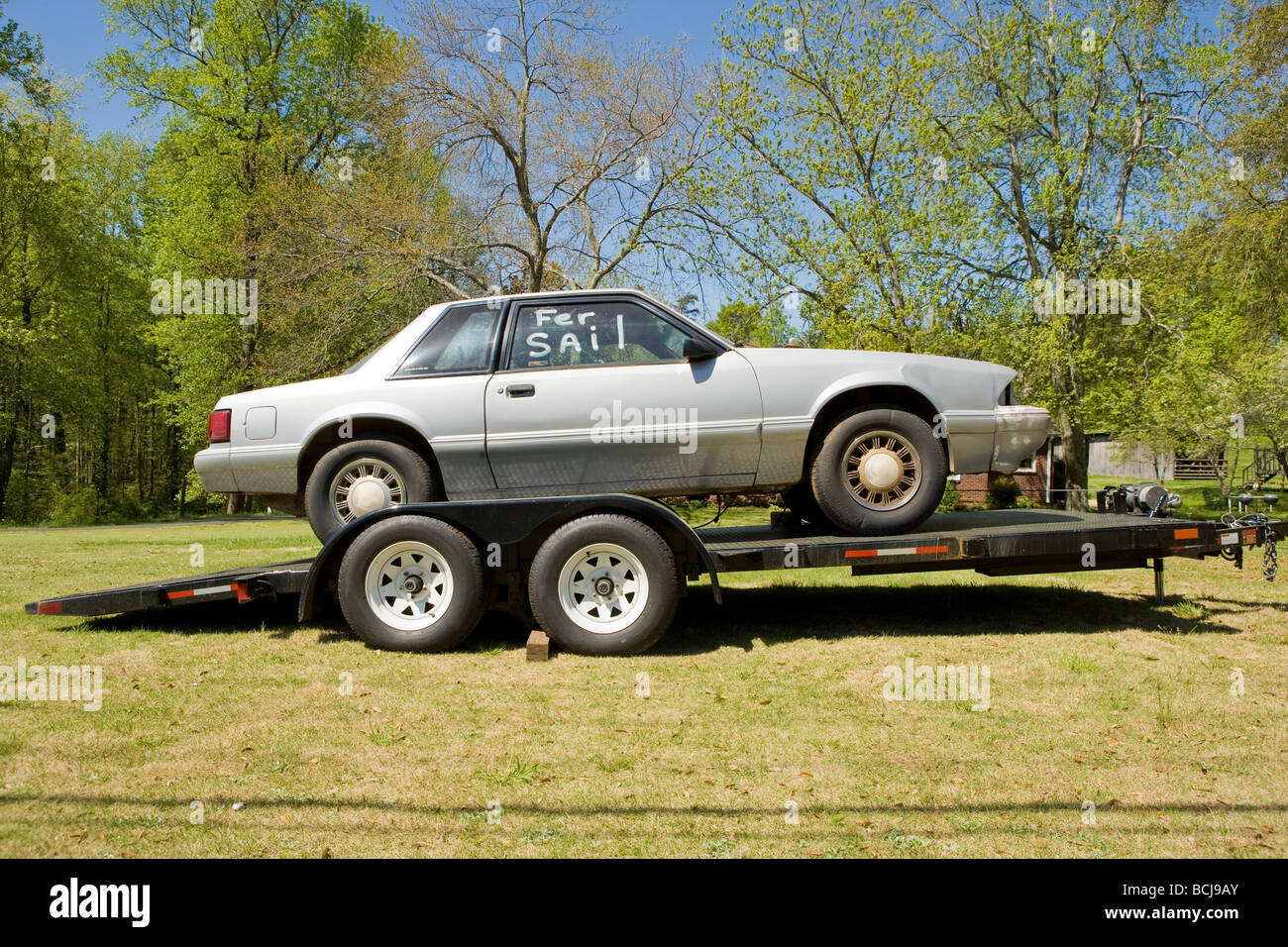 Car for sale on transport trailer carrier parked on lawn with trees ...
