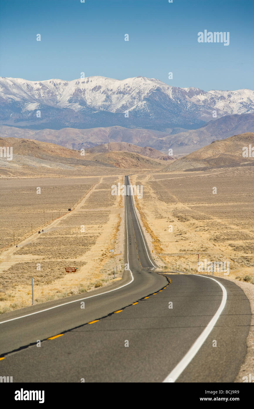 Nevada Highway 50, straight road in desert, road is known as 'Loneliest Highway in America'  Snow-capped - Stock Image