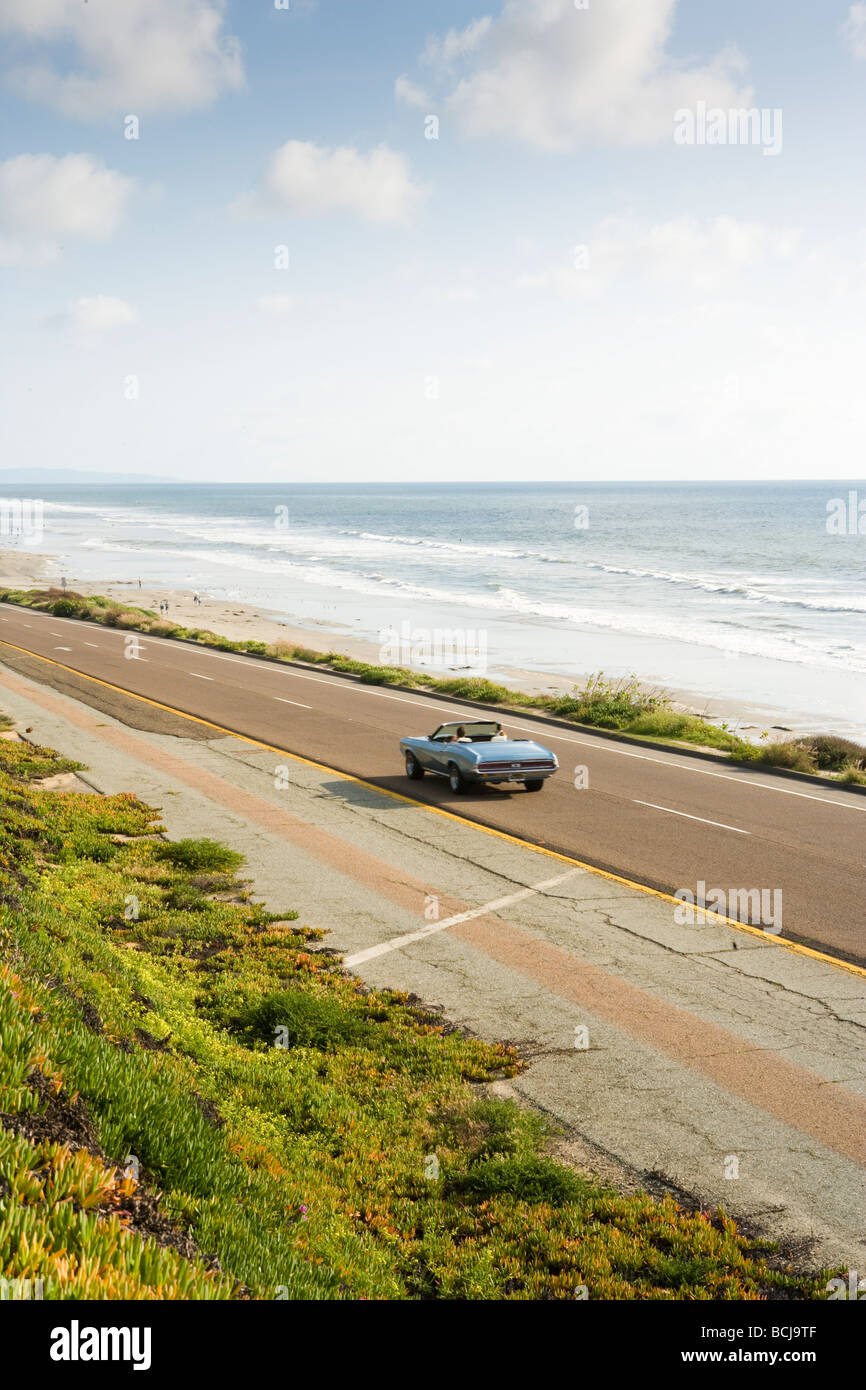 Female driving blue convertible car on highway road next to Pacific Ocean Highway 1 in Carlsbad California USA - Stock Image