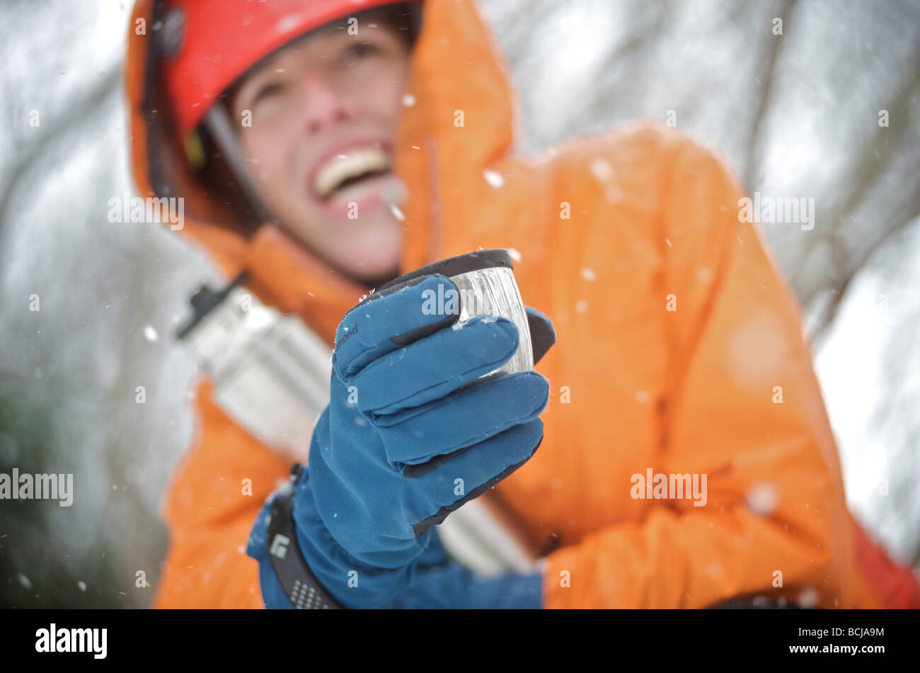 Female ice climber enjoys a hot drink during a day of ice climbing in Portage Valley, Alaska - Stock Image