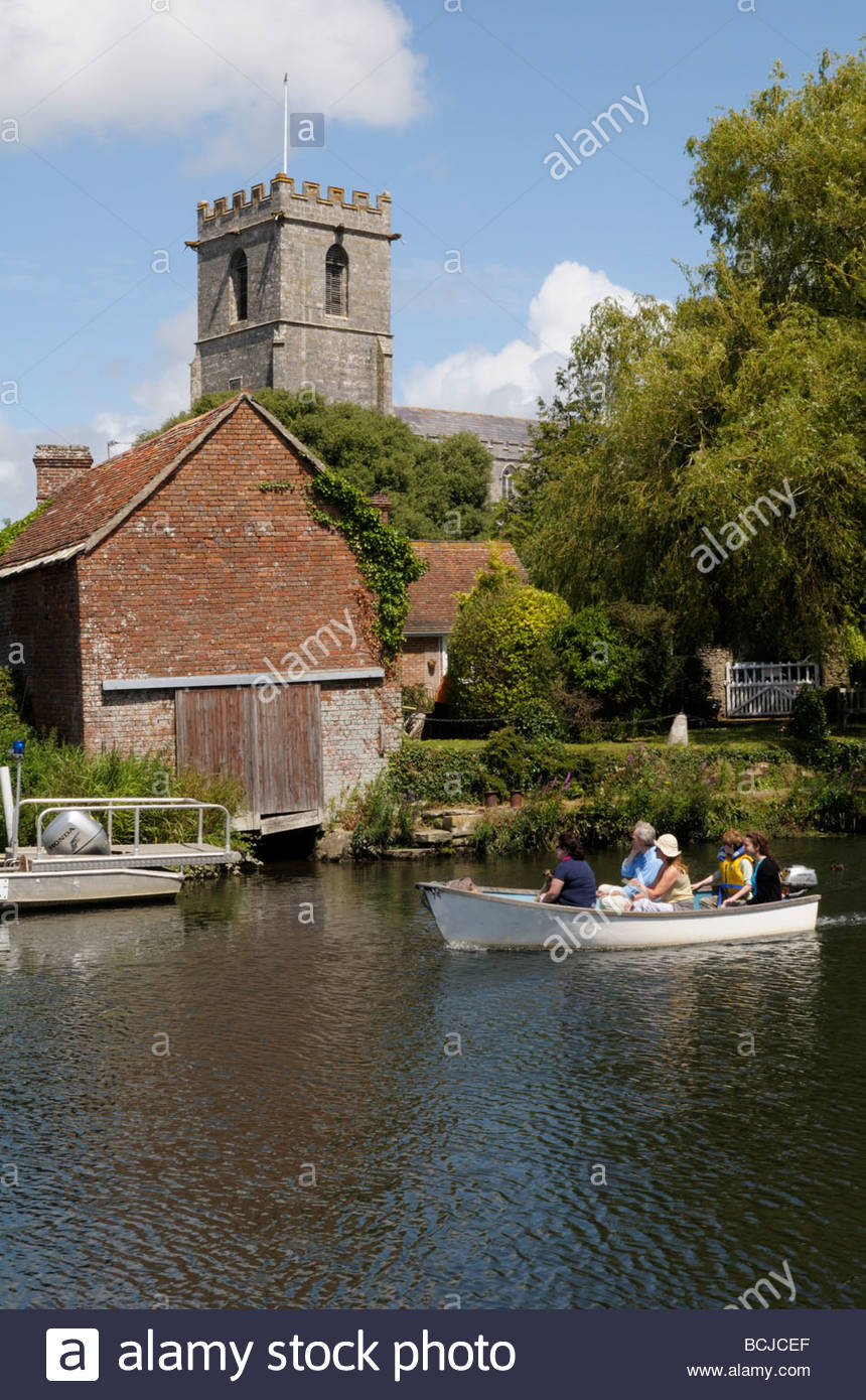 View of a day boat trip the River Frome towards the Church at Wareham, Dorset, England, UK - Stock Image