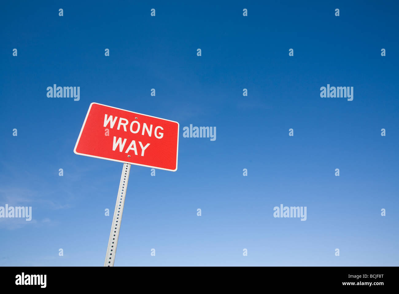 Red white WRONG WAY highway warning sign against blue sky - Stock Image
